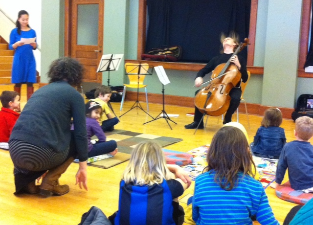 Children listen to the Chiara String Quartet at the ACMS Rug Concert.