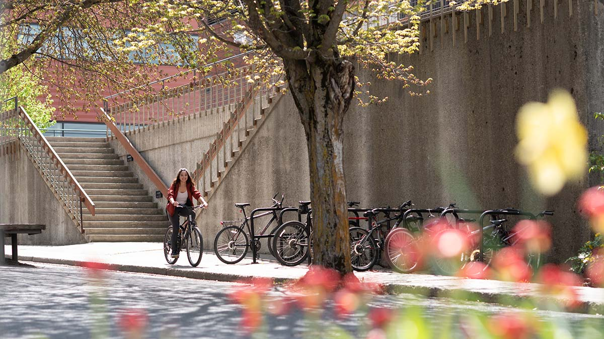 Student riding a bike with spring flowers in foreground
