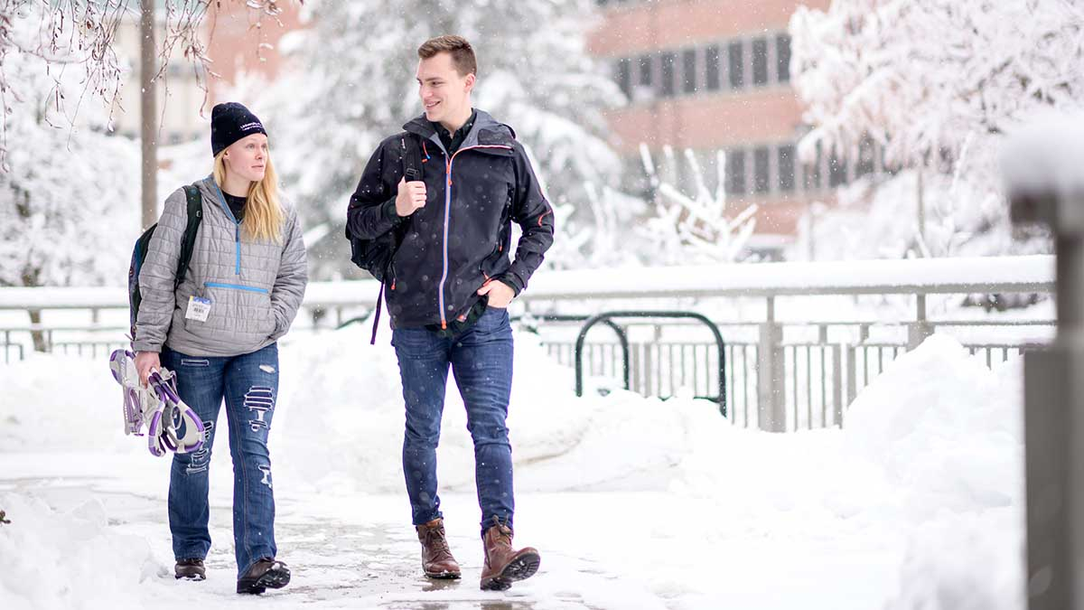 Students walking on campus while it is snowing