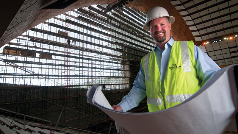 EMBA graduate and contractor holding draft drawings of the kibbie dome