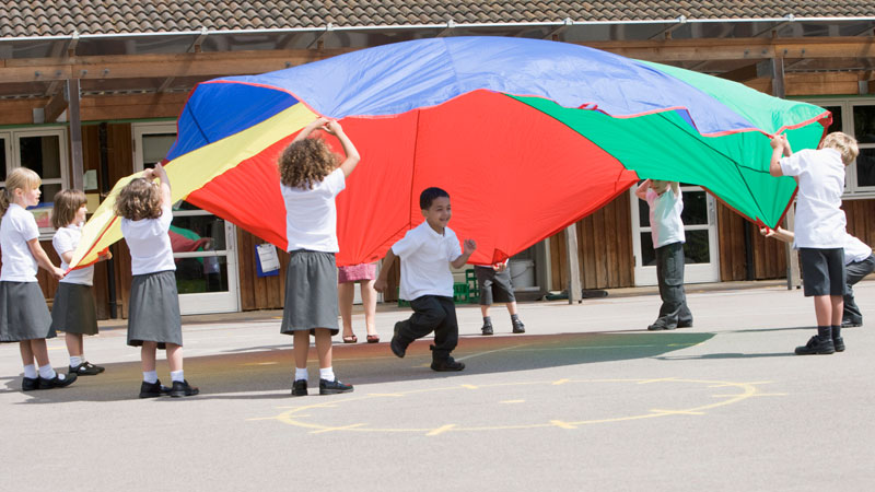 elementary students playing with a parachute during physical education class