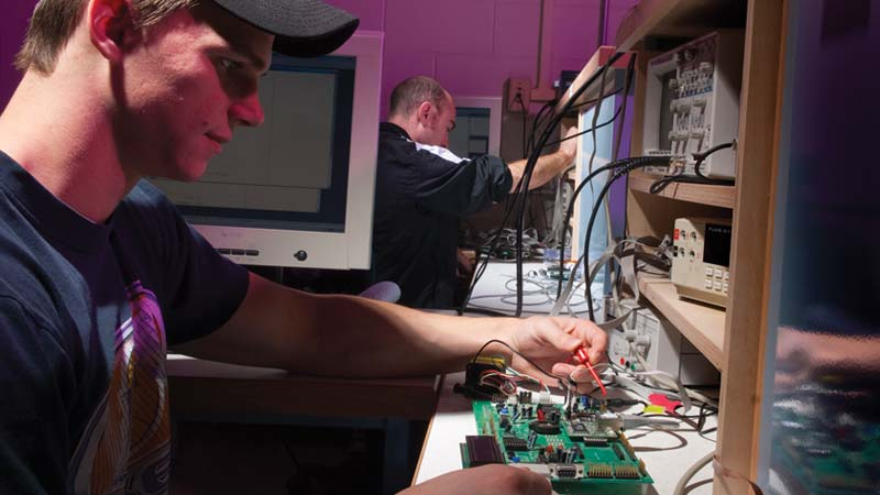 Electrical Engineering undergraduate students at the University of Idaho use an oscilloscope to measure voltage on a circuit board in a lab.