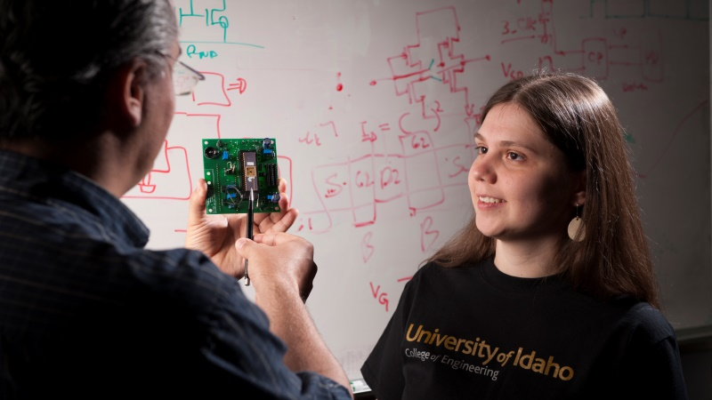 A University of Idaho Engineering student works with a professor at the University of Idaho on an electrical engineering project with a circuit board, UI offers graduate and undergraduate electrical engineering degrees.