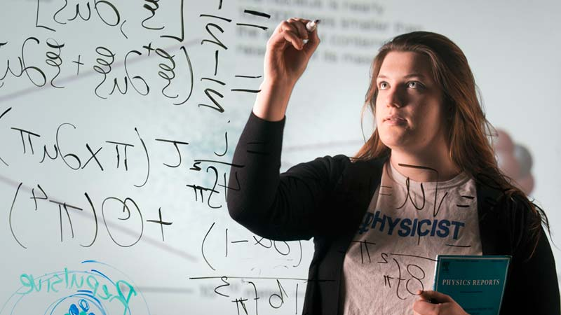 Undergraduate Physics student solving an equation at the University of Idaho.