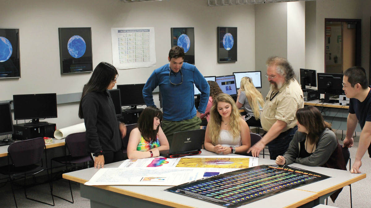 Geography graduate students working with a raised relief map at the University of Idaho