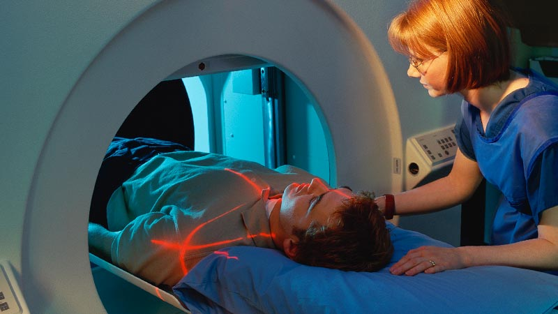A medical technician assists a patient for an MRI scan.