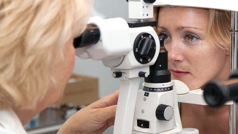 An optometrist uses a slit lamp to see a magnified view of the patient's eye.