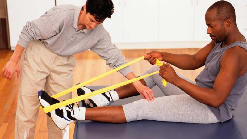 A physical therapist helps an athletic patient through physical therapy.