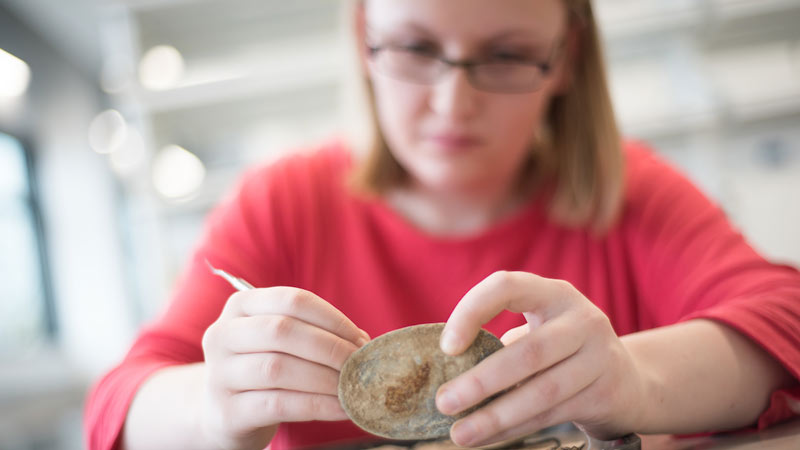 A anthropology student at the University of Idaho examines specimens in the department's artifact collections and well-equipped laboratory.