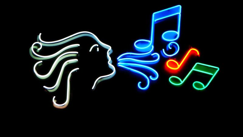 Neon light of a woman blowing out musical notes