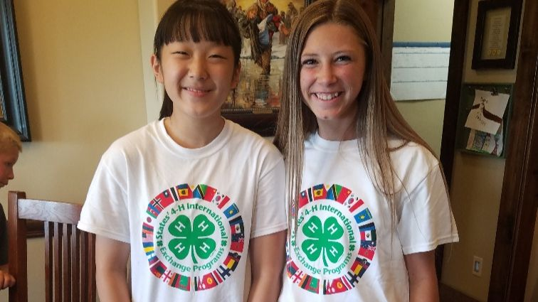 "Two teens wear matching shirts with ""States' 4-H International Exchange Programs logo."