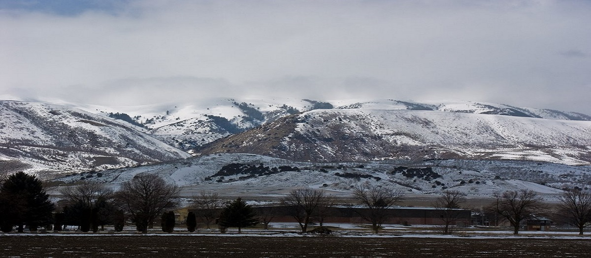 A line of mountains is covered with large patches of snow.