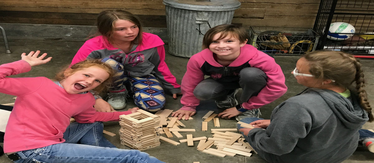 Girls are playing with Keva Planks at 4-H Camp