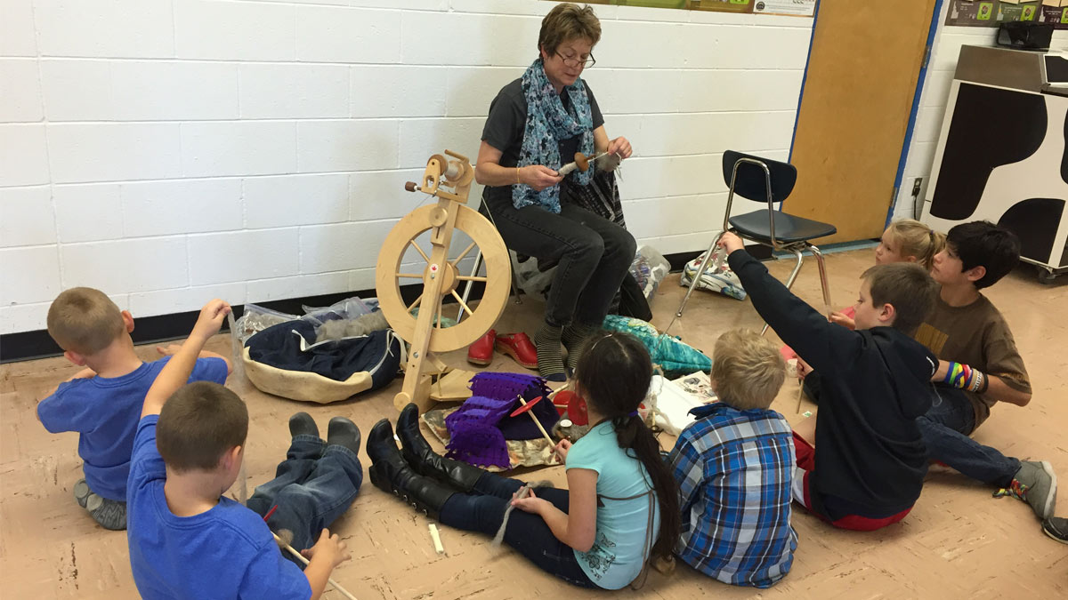 A woman makes thread on a spindle while children with fiber and spindles of their own look on.