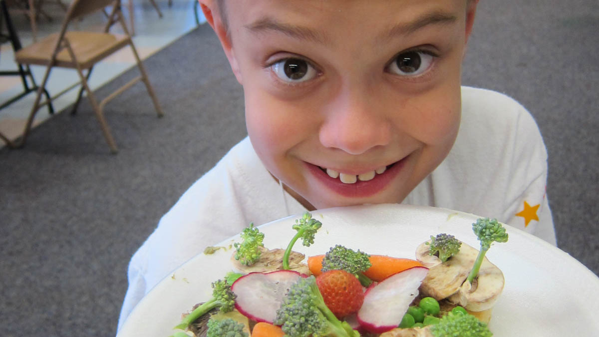child holding a plate of vegetables that looks like trees, a jungle