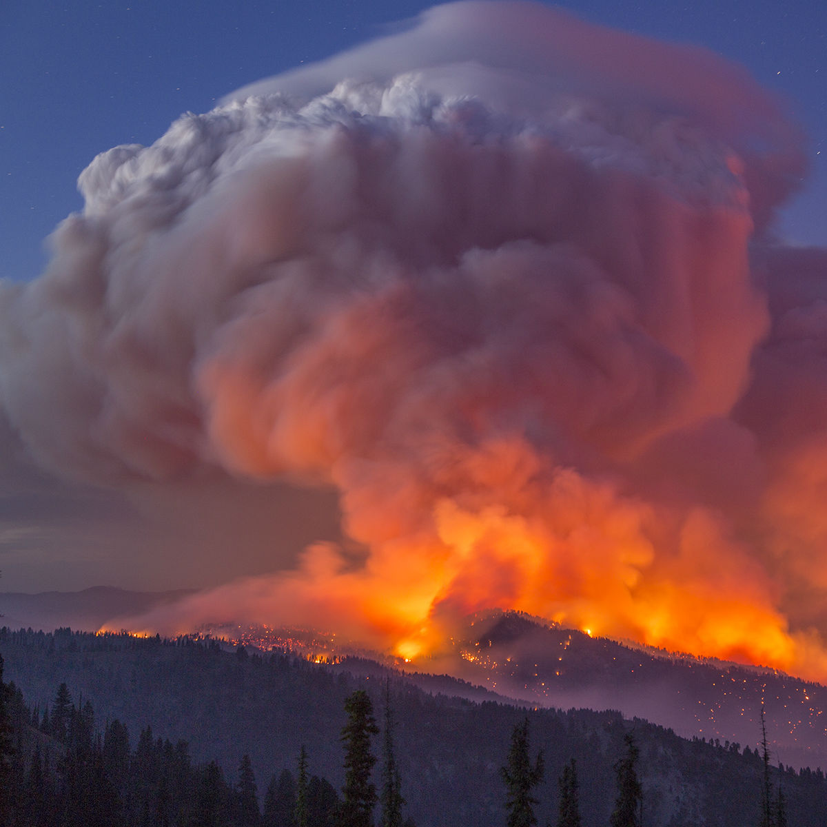 A column of smoke rises from a mountain on fire.