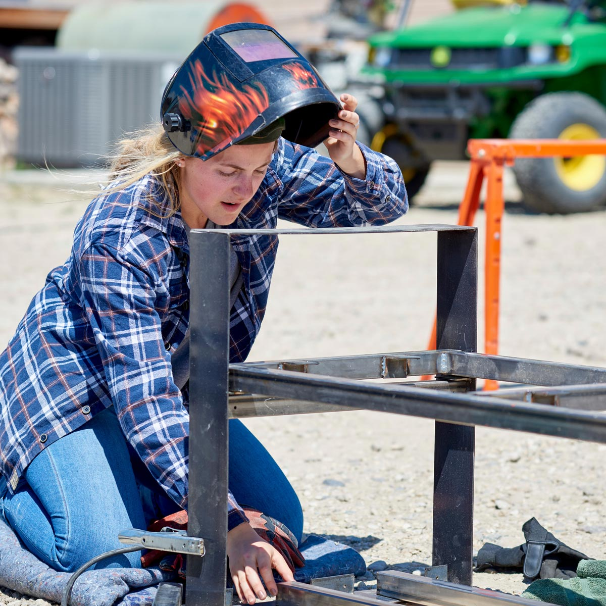 A student lifts her welding mask to inspect her work.