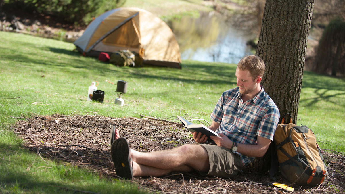 A student leans against a tree and reads a book at Taylor Wilderness Research Station.
