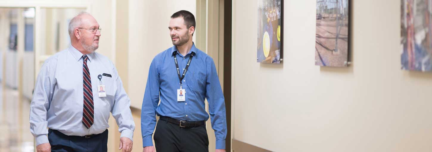 Luke Hill and a supervisor walk the halls of Schweitzer Engineering Laboratories