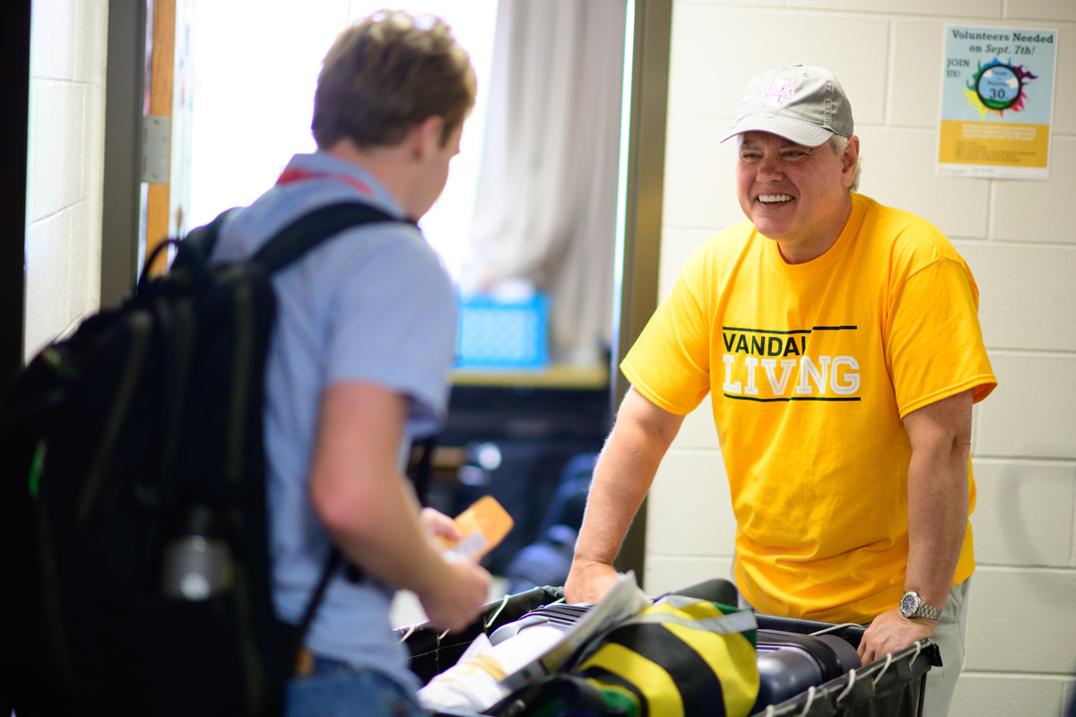 Scott Green, a freshman president, greets just-arrived freshmen as they move into residence halls.