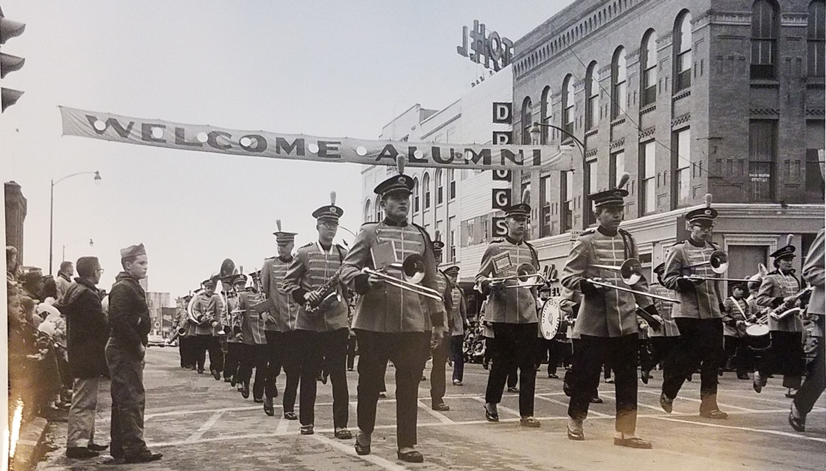 The marching band marching in the Homecoming parade in the 1950s.