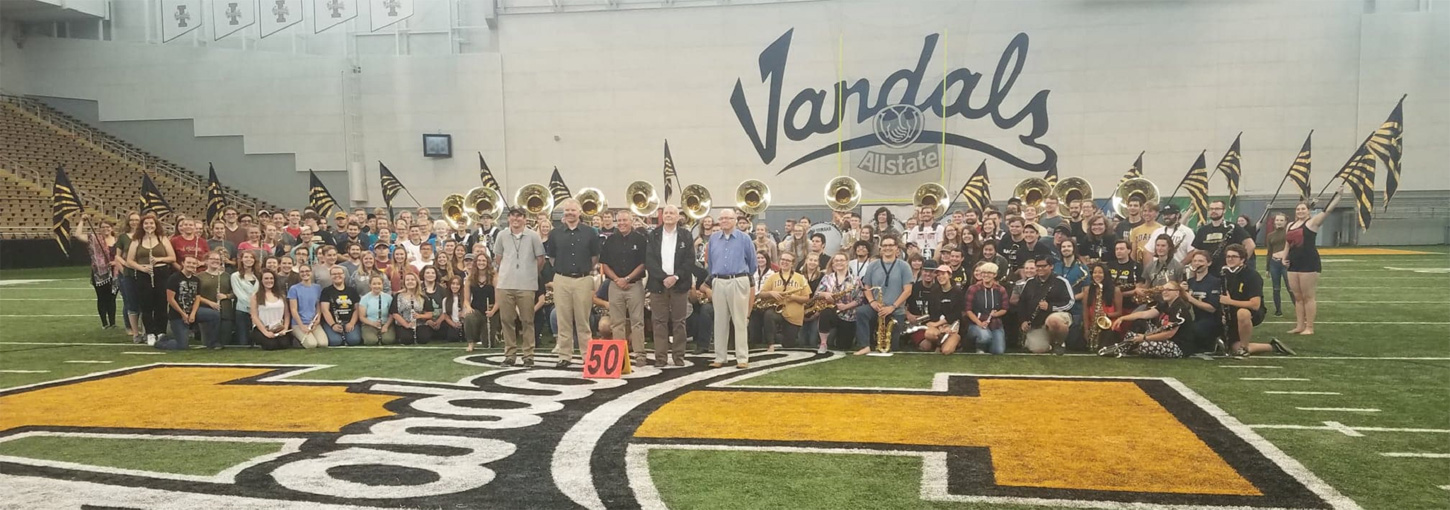 five band leaders stand with the marching band on the 50 yard line