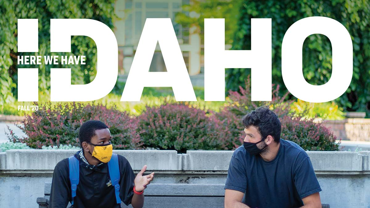 The cover of Here We Have Idaho fall 2020: two students wearing masks, sitting on opposite sides of a bench and holding a conversation.