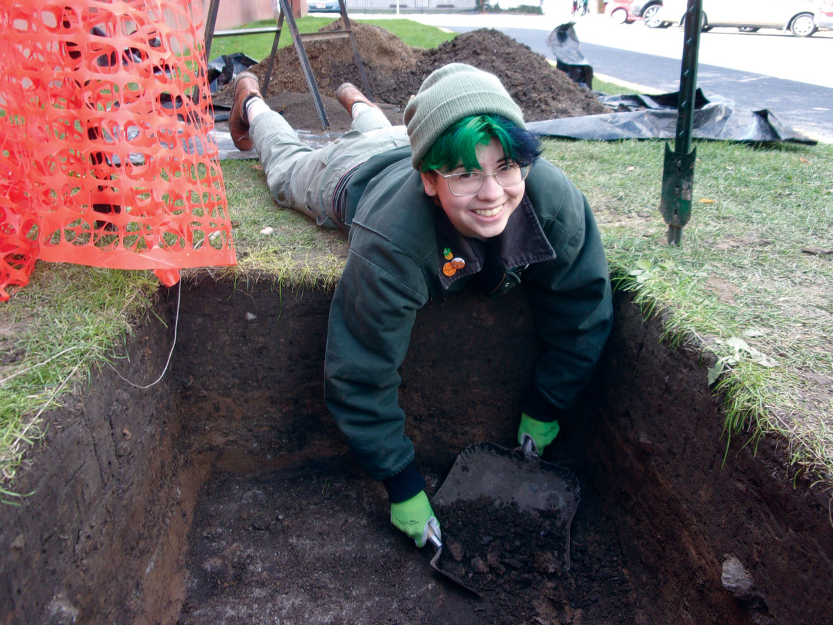 A volunteer excavates for artifacts outside of Moscow High School.