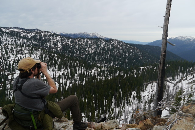 Jack Kredell looks through binoculars while sitting on a rock overlooking the Selkirk Mountains.
