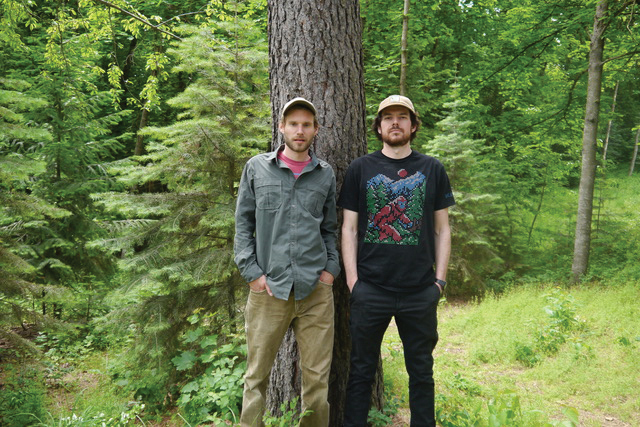 Chris Lamb and Jack Kredell stand by a tree in the woods.