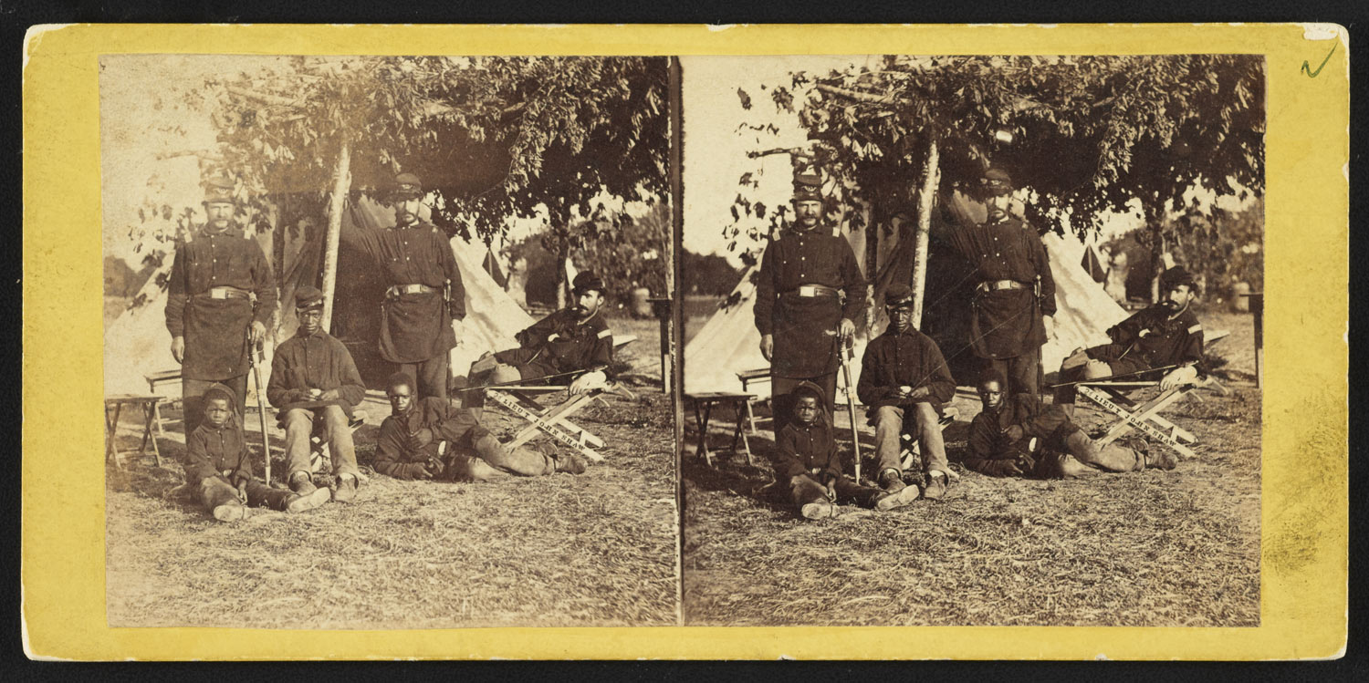 Stereograph showing Capt. B.S. Brown (left); Lt. John P. Shaw, Co. F 2nd Regt. Rhode Island Volunteer Infantry (center); and Lt. Fry (right) with African American men and boy at Camp Brightwood, D.C..
