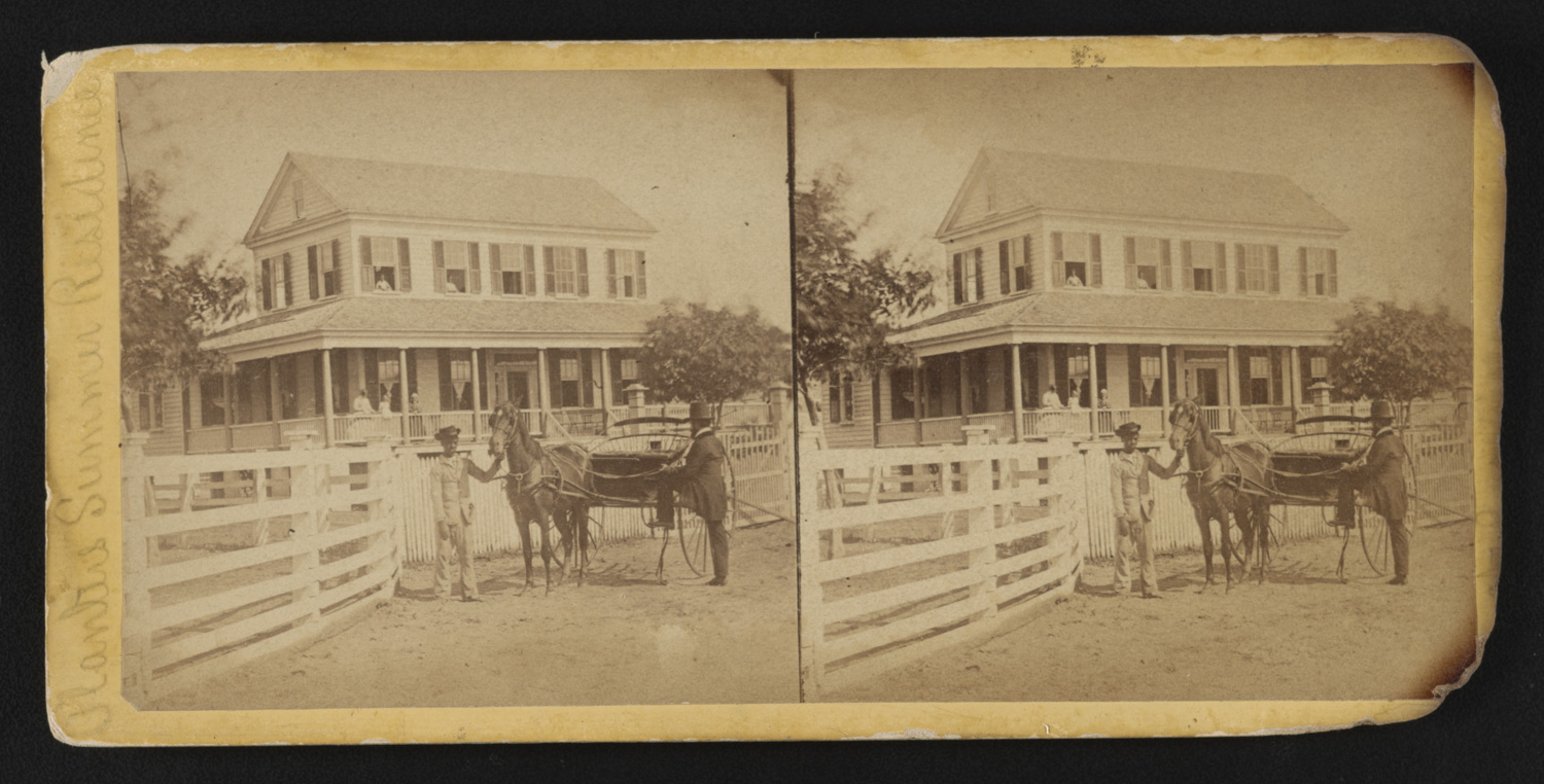 an African American boy holding on to the horse drawn carriage in front of a planter's house. A man prepares to board the carriage.