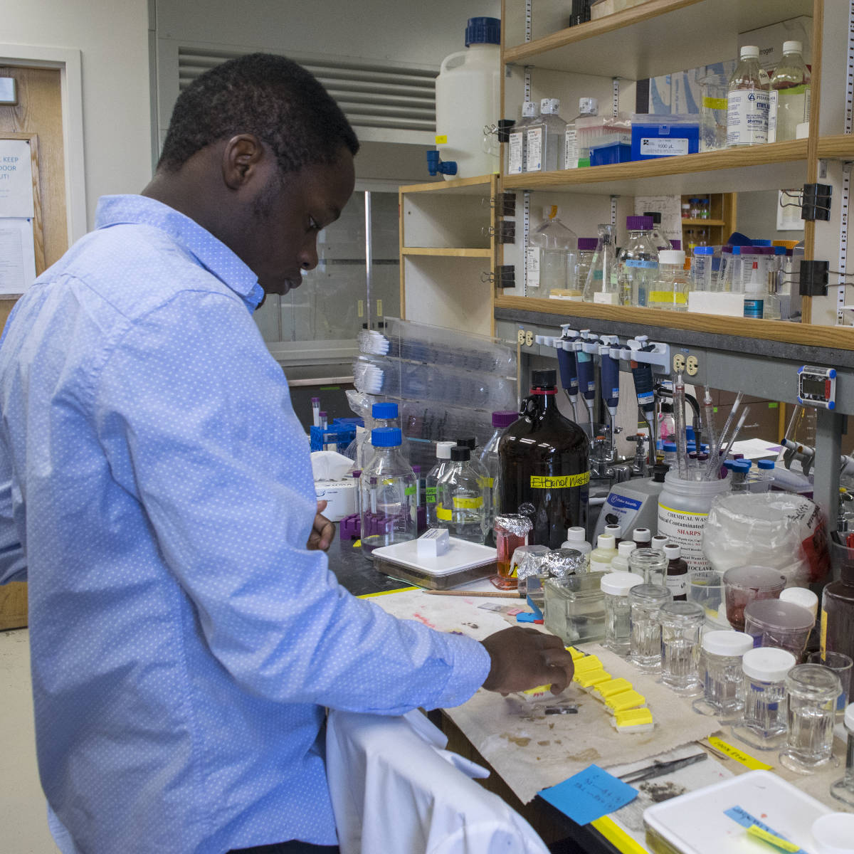 Emmanuel Ijezie prepares microscope slides at a crowded lab bench.