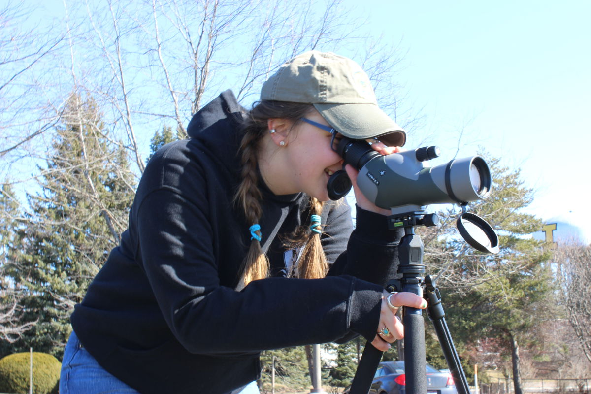 Katie Anderson bends down to look through her telescope.