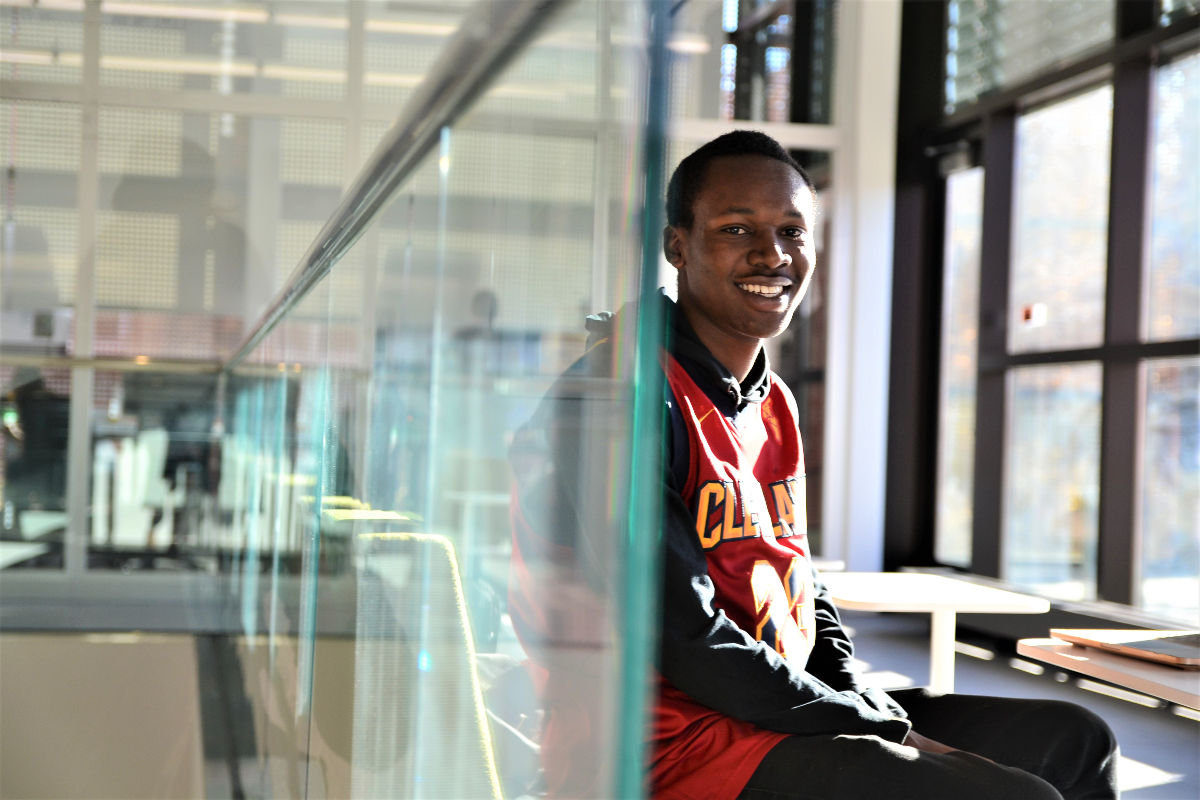 Fredrick Shema sits against a glass wall in the Integrated Research and Innovation Center.
