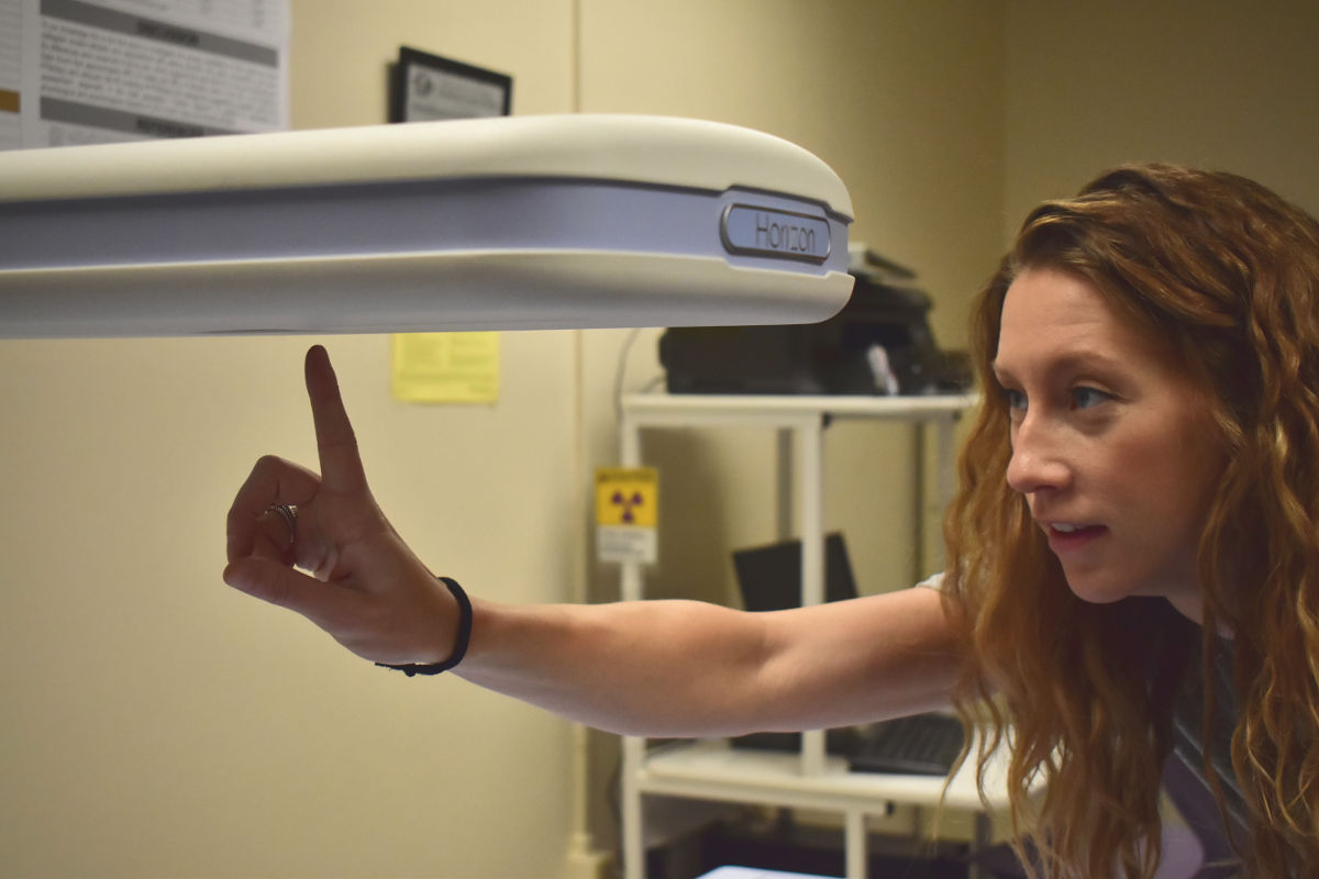Ann Brown points at a portion of the dual-energy X-ray absorptiometry machine in the Human Performance Lab.
