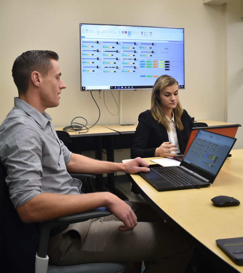 Lucas Rovic and Alexandra Malfant sit at a table with their laptops. An image of their research data is displayed behind them.