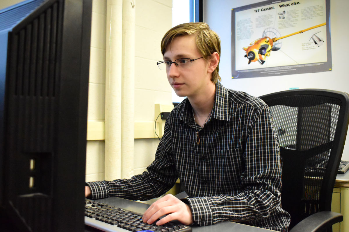 Samuel Myers sits at his desk working on a computer.
