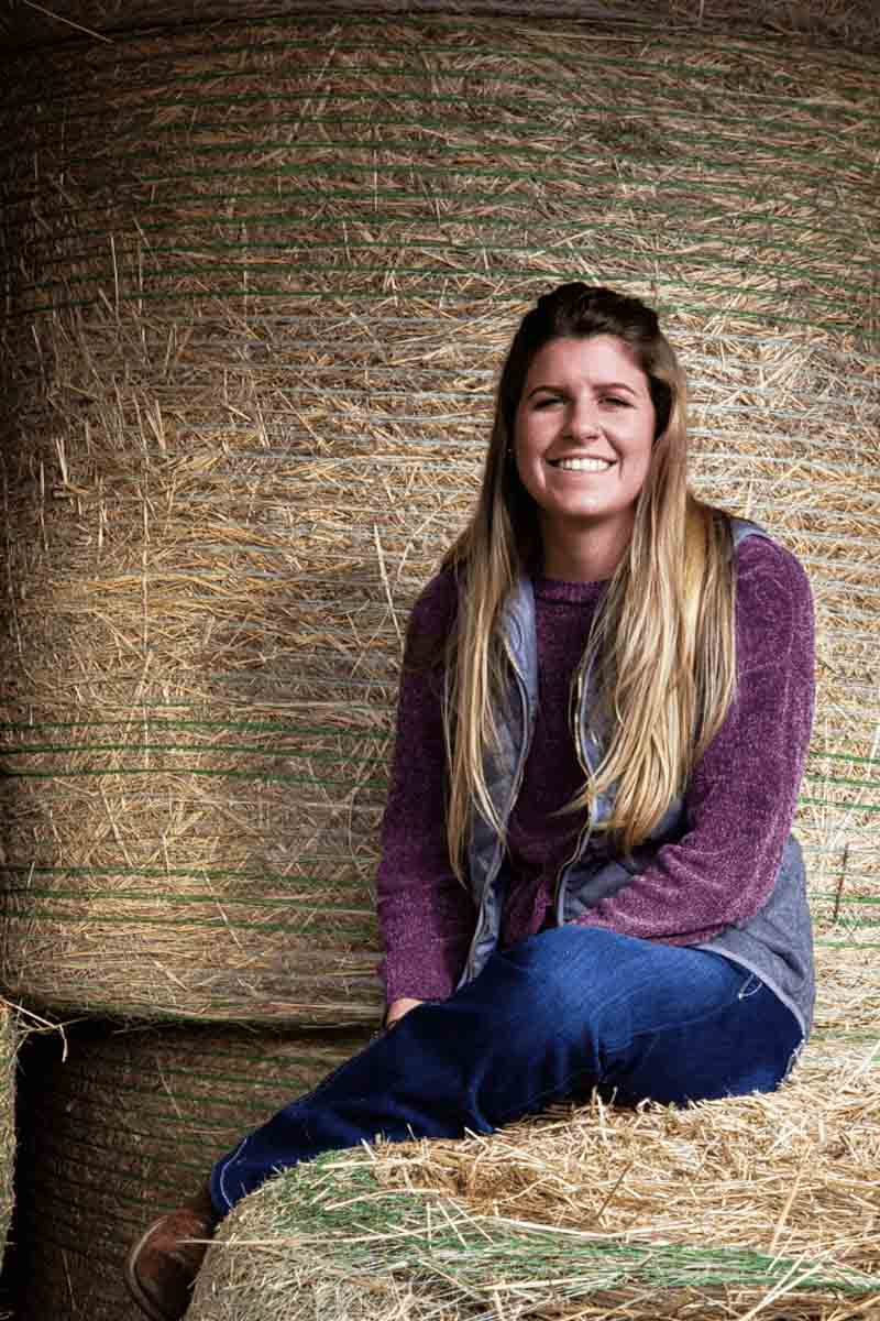 Chanelle Brusseau sits on hay bale by the U of I Beef Center.