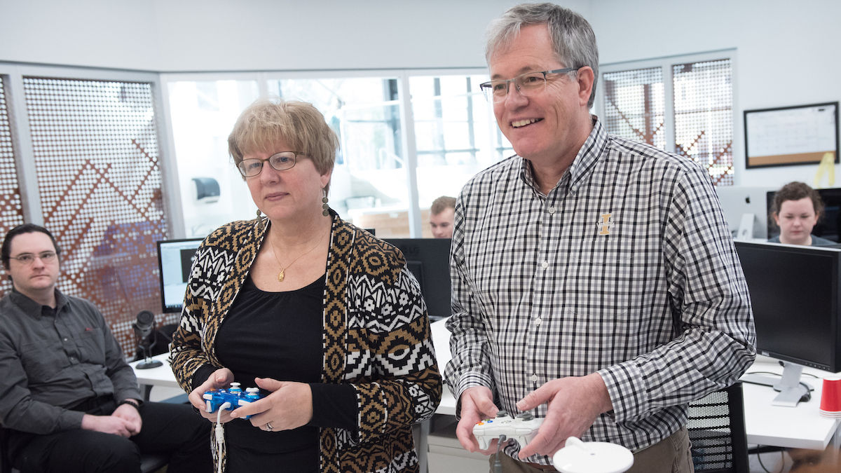 U of I President Staben and ORED Vice President Janet Nelson play a video game