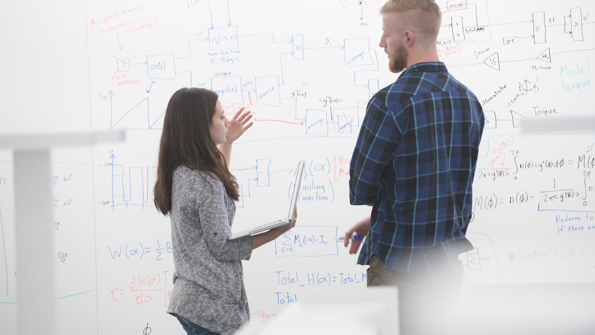 Two people stand in front of a whiteboard having a discussion