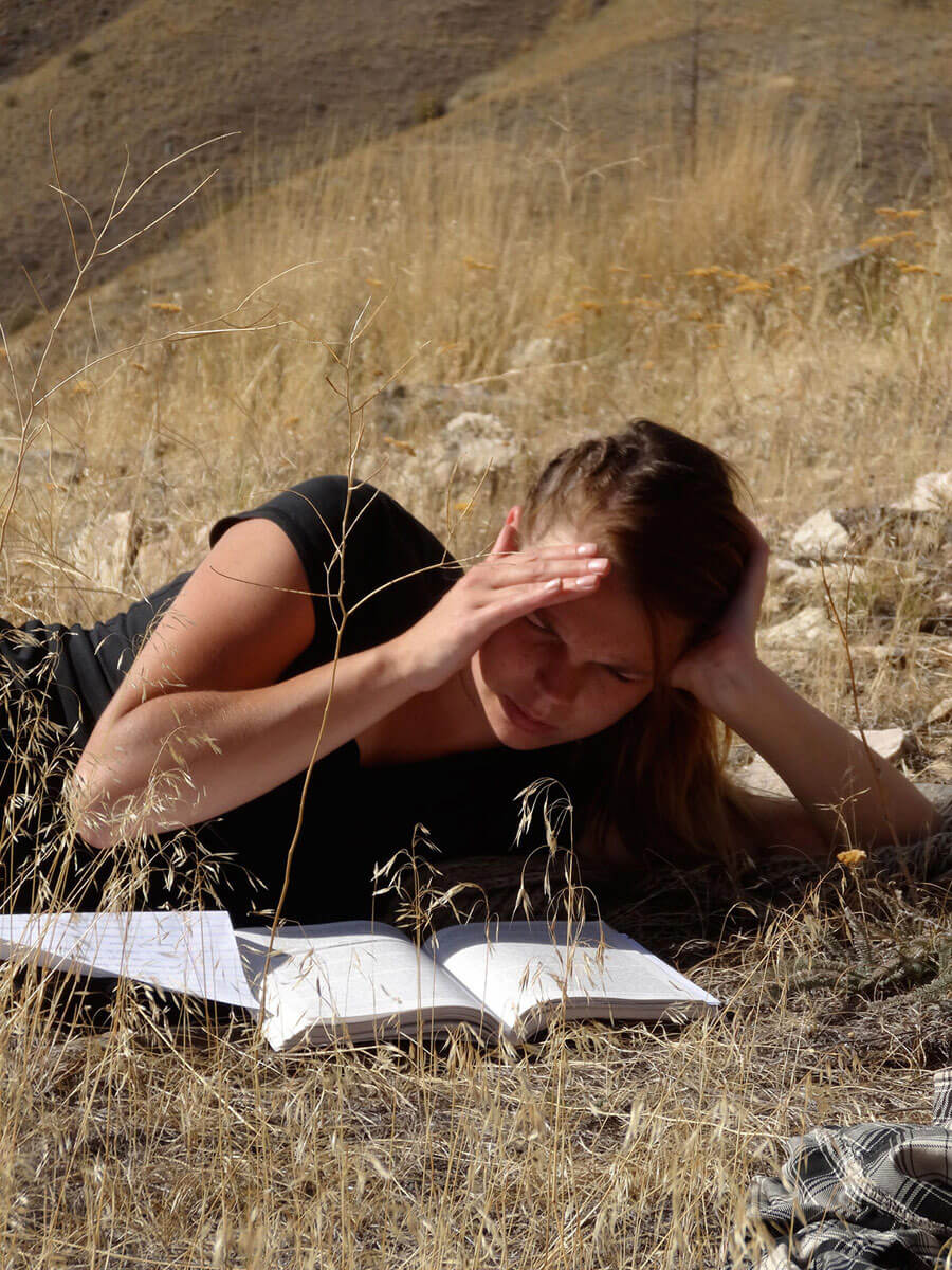 A student reads her notebook in a field.