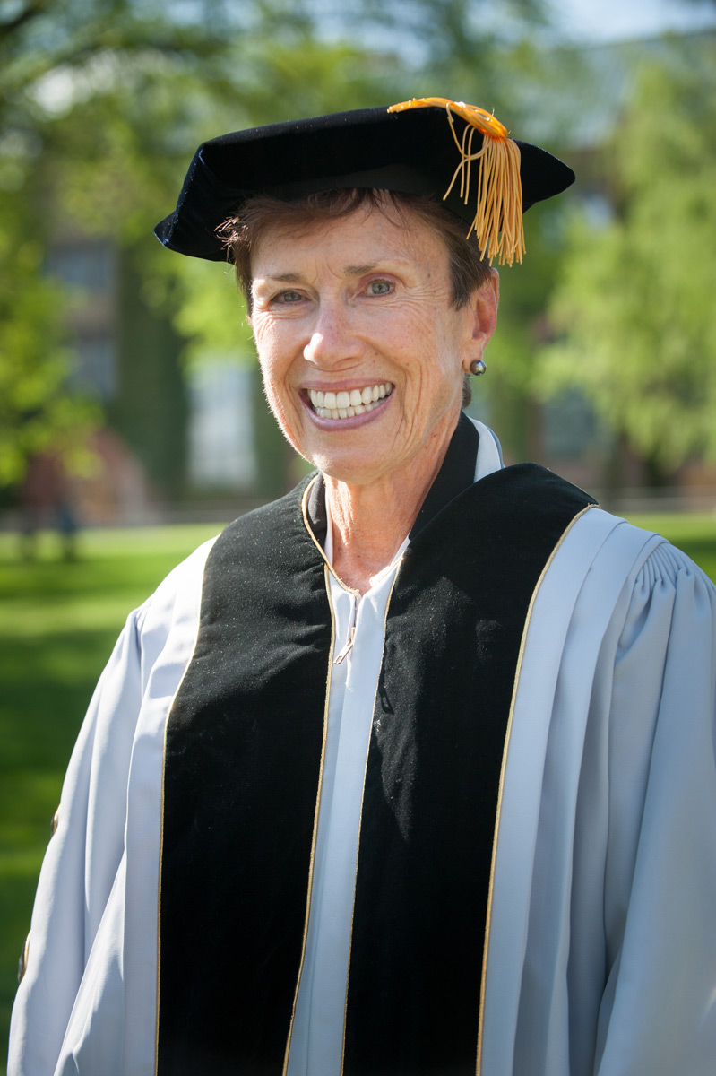 Judith Runstad wearing commencement robes on the Admin Lawn.