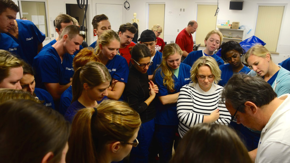 The crowd of students watch the suturing techniques of Dr. Hall.