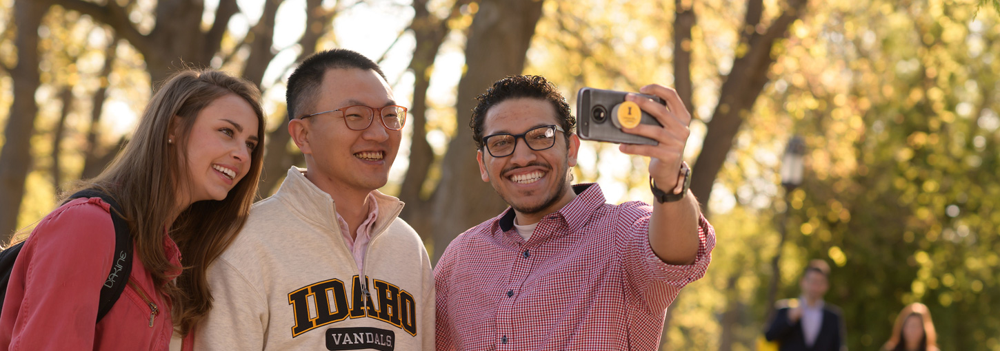 A student takes a selfie with two friends on the Administration Lawn.
