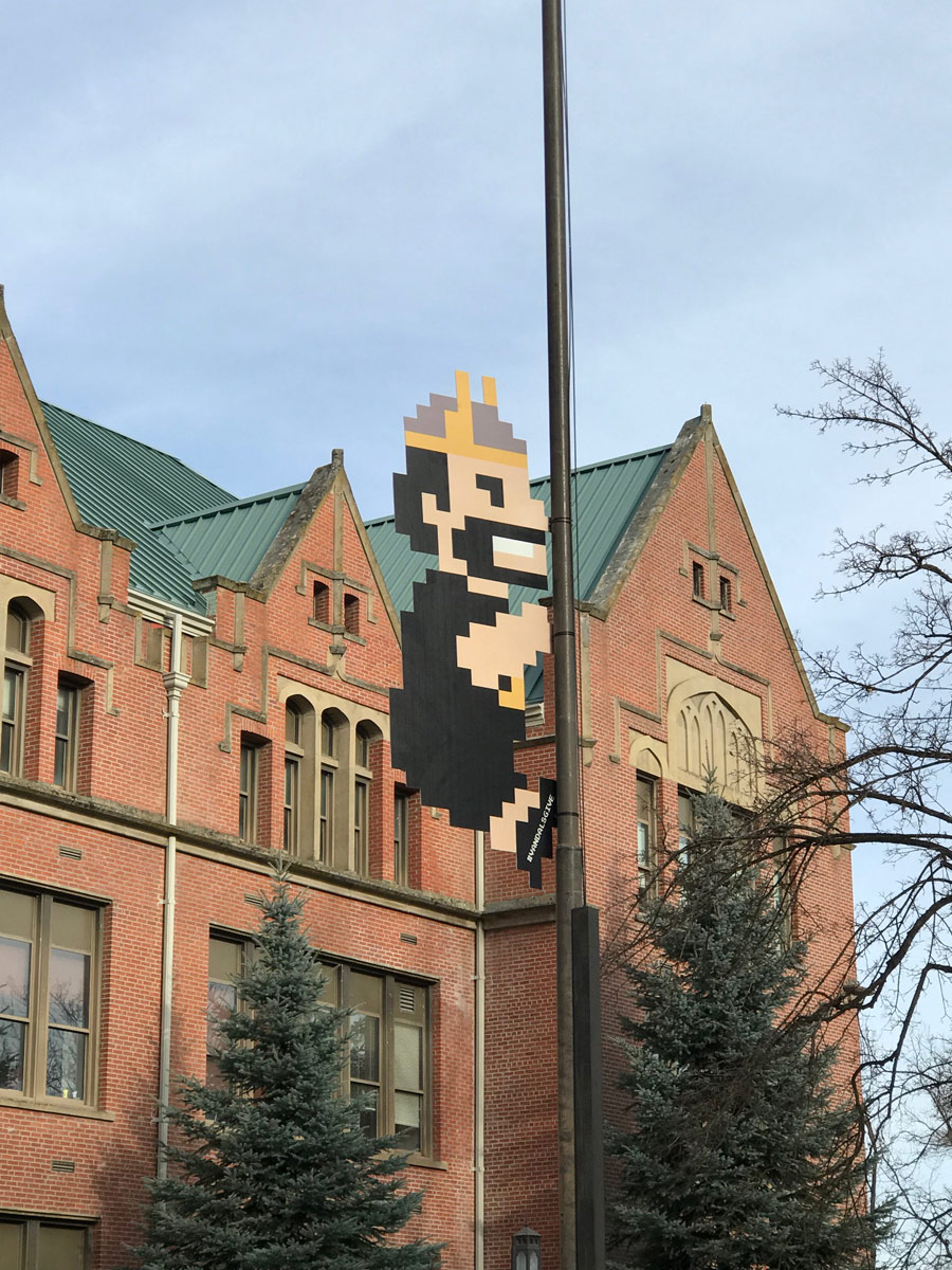 8-bit Joe Vandal climbs the flagpole in front of the Administrative Building.