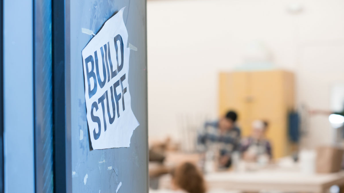 "A blue wall with a sign reading ""Build Stuff."" A design studio is visible in the background."