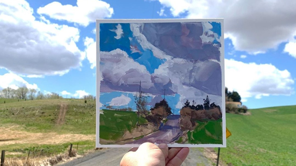 Aaron Johnson holds a painting in his hands outside, with green grass, hills and clouds in the blue sky.