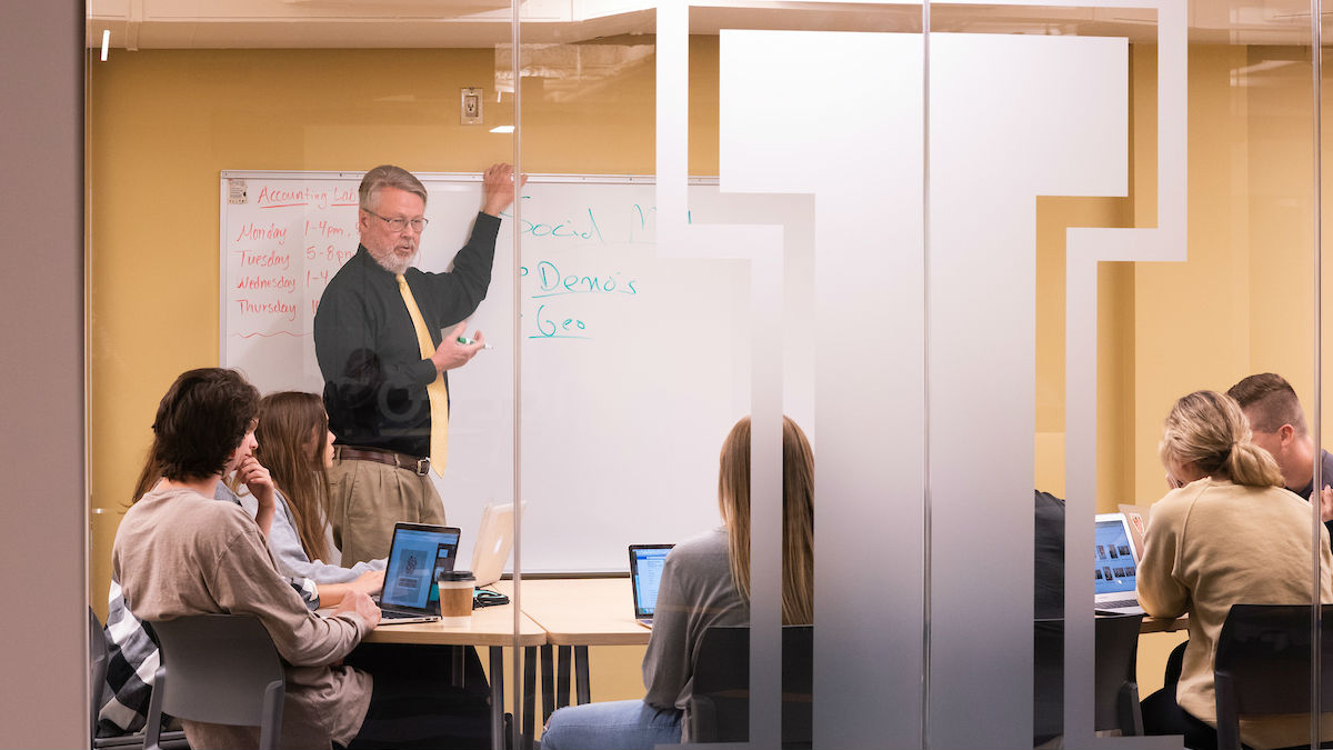 Mike McCullough, professor in the Marketing department, leads a study session in a remodeled conference room in the Albertson building basement.