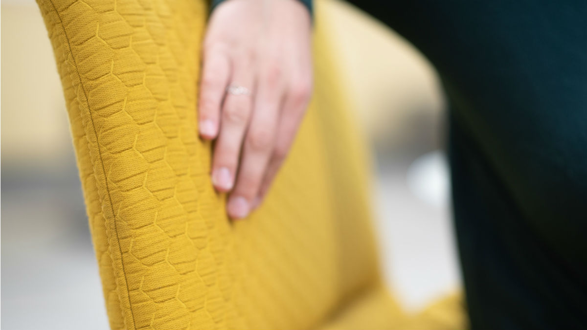 A student's hand feels the upholstery on a new pride gold chair.